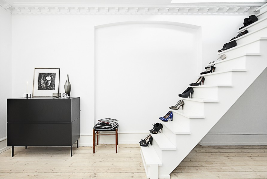 A white room and white staircase with womens shoes displayed on each step